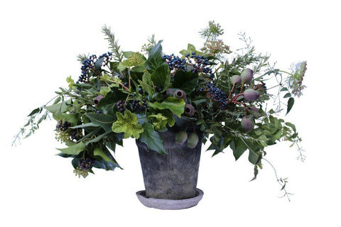 Grey terracotta vase filled with fresh cut greenery, pods and berries.