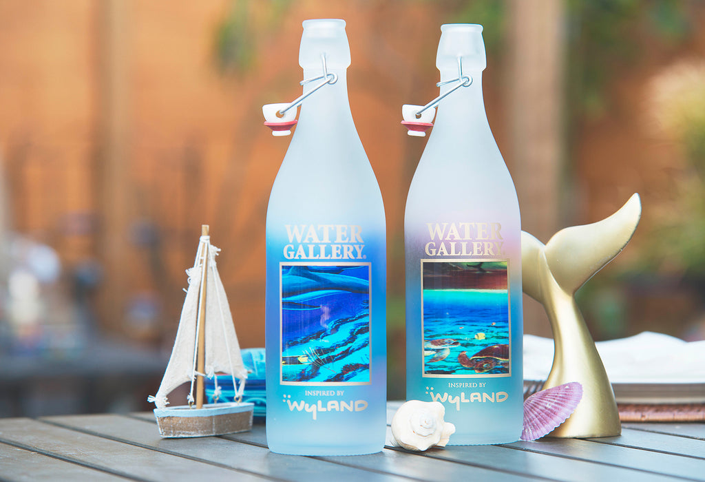 Gorgeous Wyland glass water bottles and shells, gold whale tail art piece, and mini sailboat