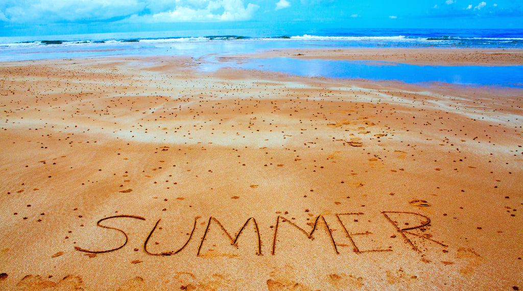 the word summer written on the brown sand with blue sky and water in the background