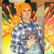 Surf lifestyle artist Drew Brophy surrounded by his incredible, colorful paintings