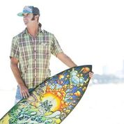 Surf lifestyle artist Drew Brophy holds one of his beautifully decorated surfboards.