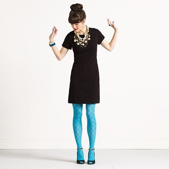 Woman in a black dress and teal leggings