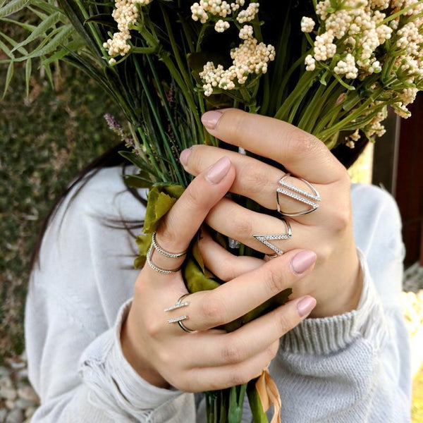 woman holding a bouquet of flowers wearing the Geometric Ring Set from Eternal Sparkles