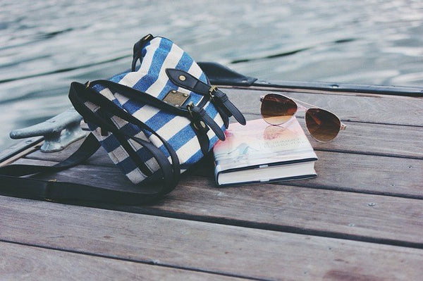 striped bag with book and sunglasses