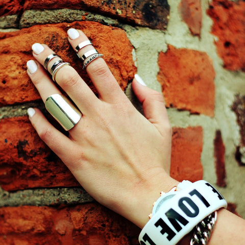 hand with rings and bracelet on a brick wall