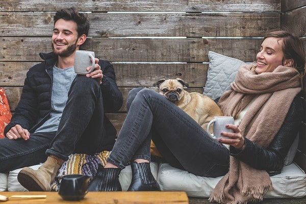 man and woman with a dog drinking coffee