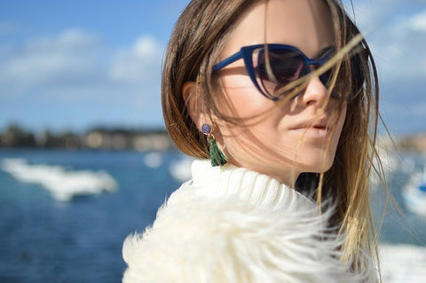 woman in dark sunglasses and tassel earrings