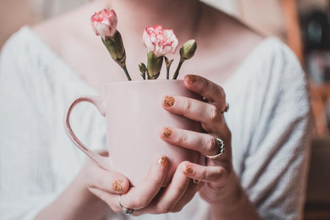 woman holding a mug with flowers inside