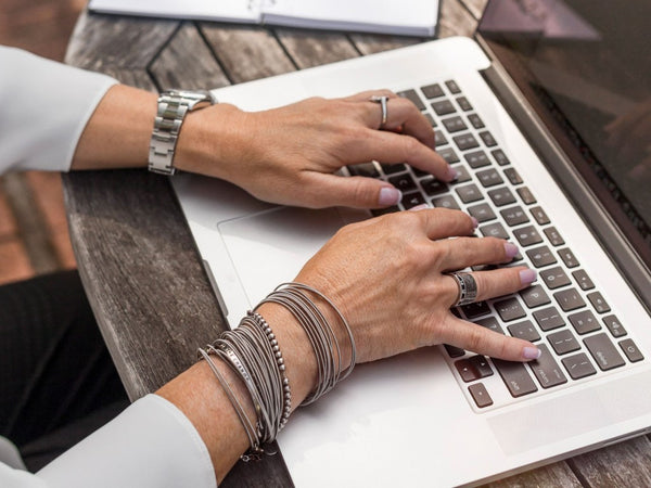 woman working on her laptop wearing bracelets and rings