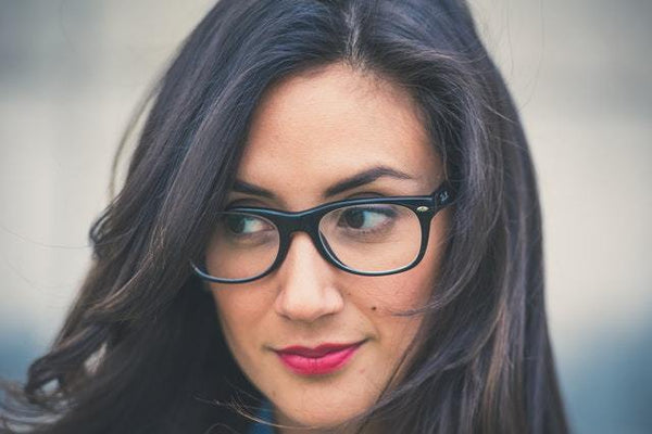 close up photo of woman with black framed eyeglasses and red lipstick