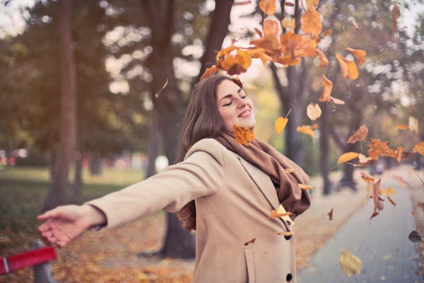 woman playing with autumn fallen leaves