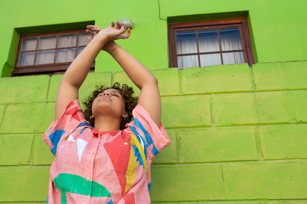 woman wearing a bright colorful top against a bright green wall