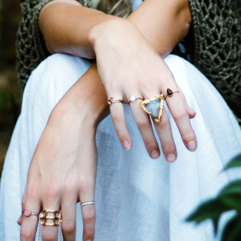 woman's hands wearing layered fashion rings