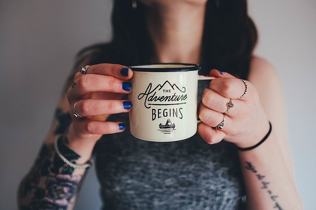 woman with tattoos and minimalist rings holding a cup