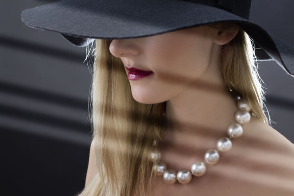 woman wearing a black hat and oversized pearl necklace