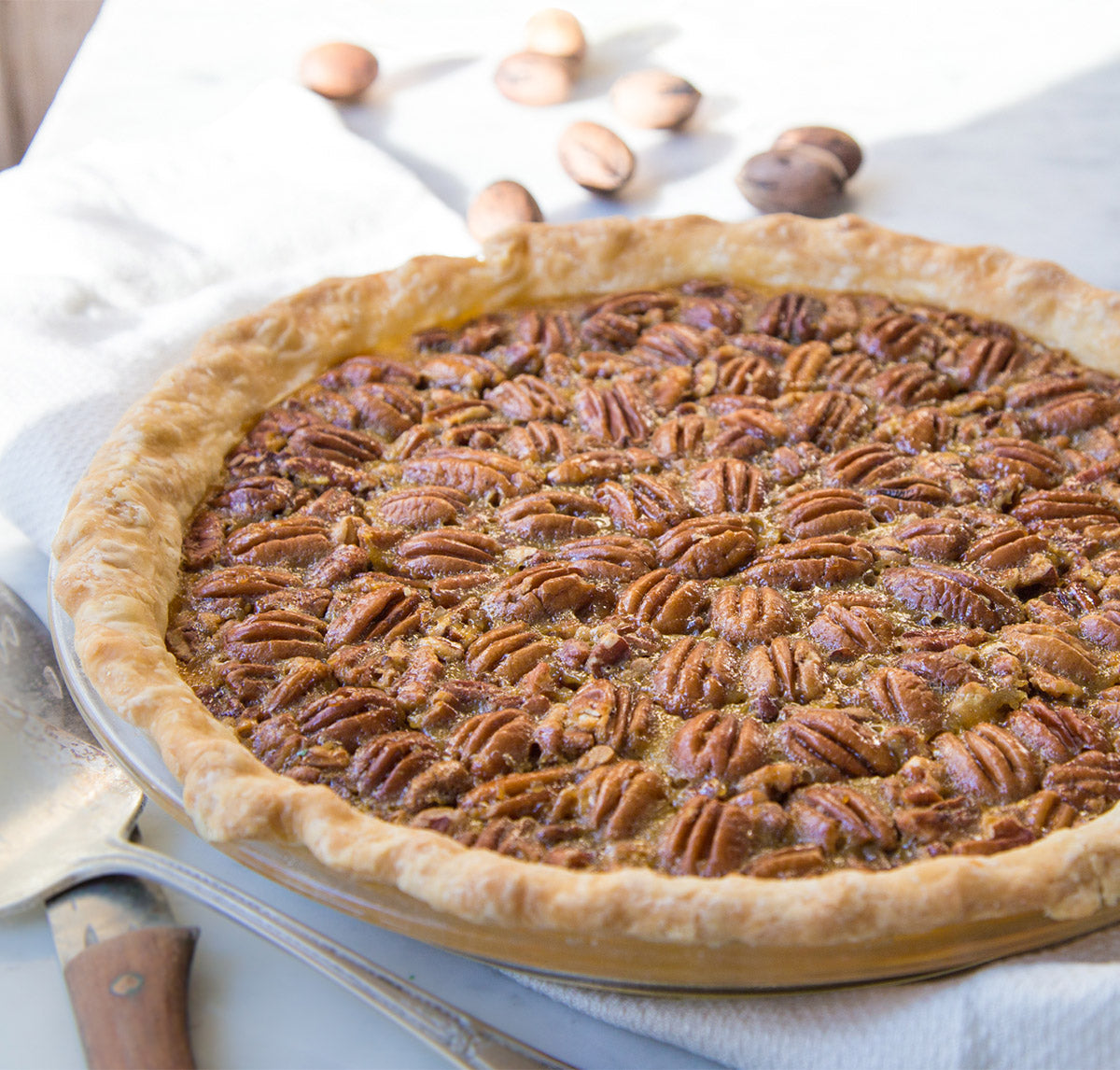 heirloom-grits-pecan-pie-whole-with-knife-and-pie-server