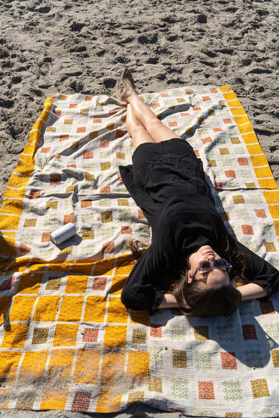 girl on beach wearing black cotton gauze dress laying on a patchwork blanket