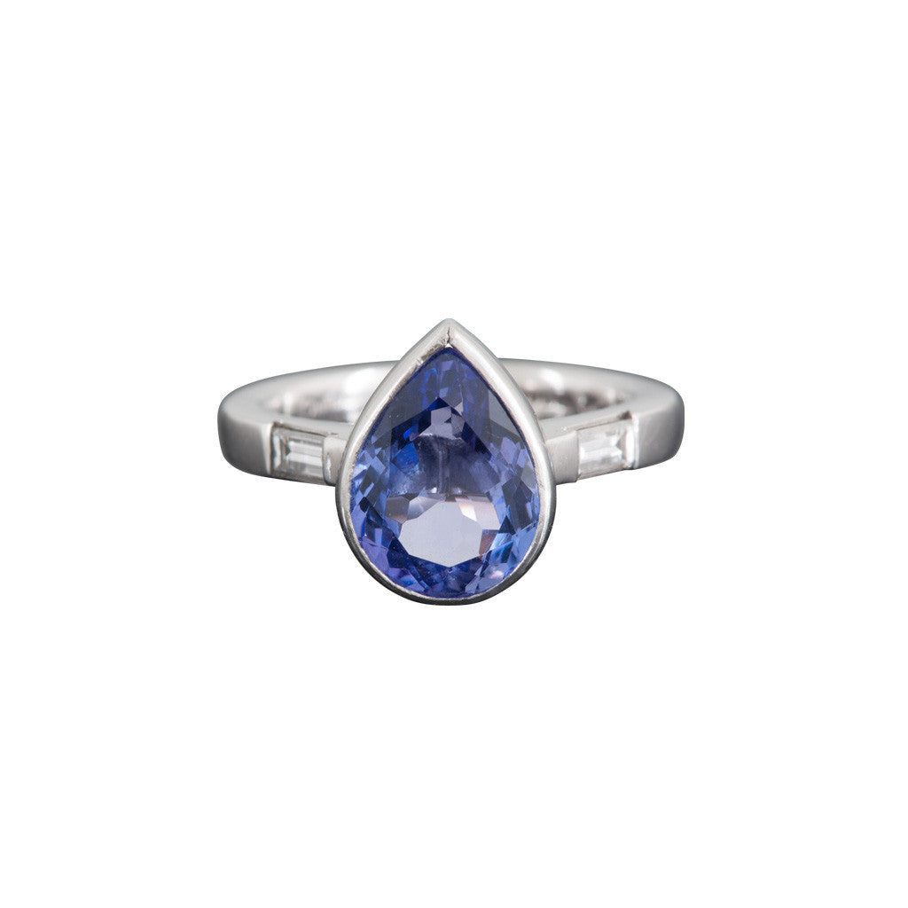 A platinum and collet-set pear shaped tanzanite ring with baguette diamond-set shoulders
