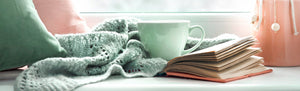 image of a cup, blanket and a book