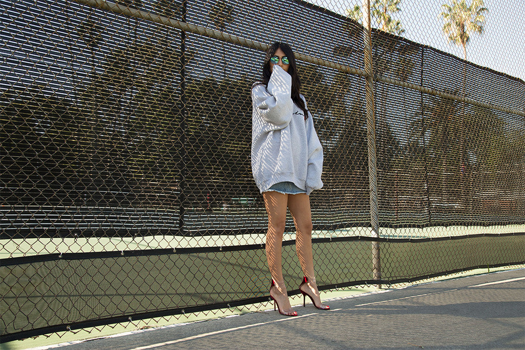 Image of model wearing grey sweater with blue jean skirt standing next to a tennis court.