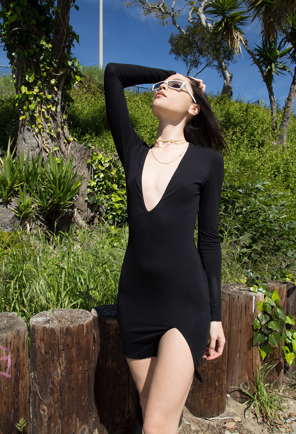 Image of model wearing a black DASH Label long sleeve dress with sunglasses.