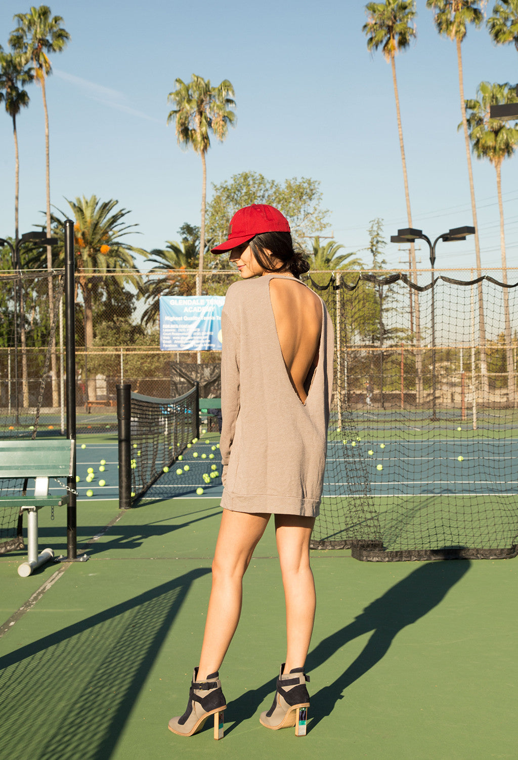 Image of model wearing DASH Label tee dress on tennis courts.