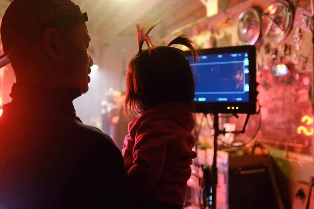 "Luis Guanzon holding his daughter behind the scenes of Quincy's ""Snuggle Up"" Music Video"