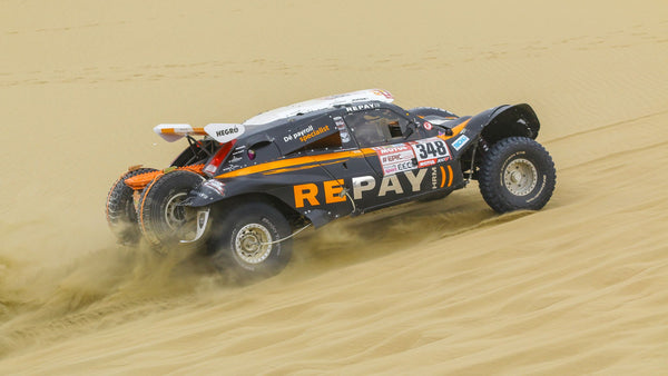 Dakar Rally car driving through sand in Saudi Arabia