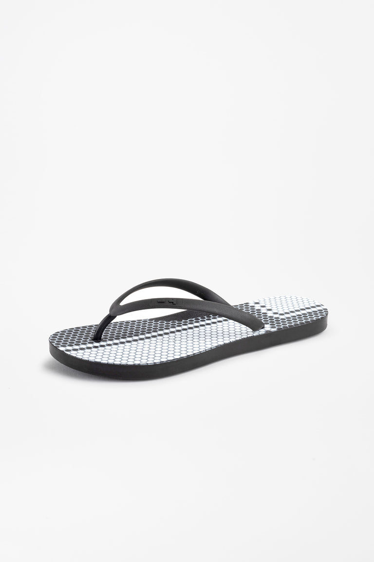 Side view of black flip flops with tile pattern