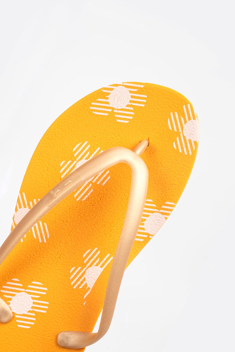 Women's orange flip flops with floral pattern.