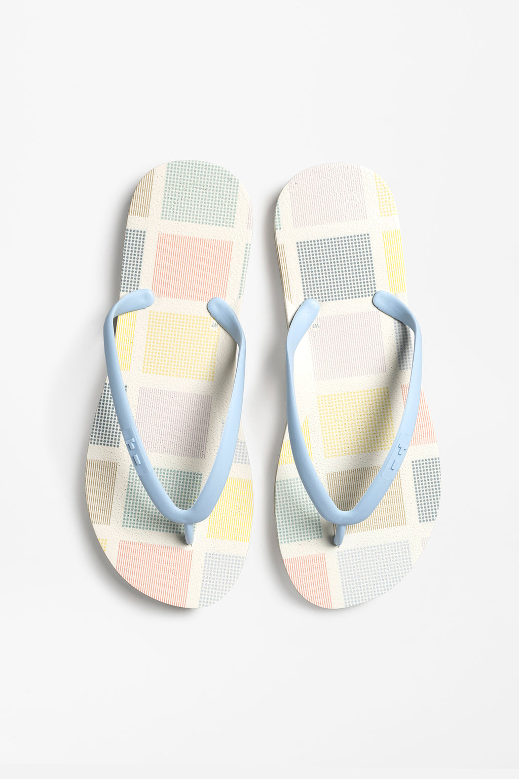 Women's white flip flops with blue strap and color block pattern