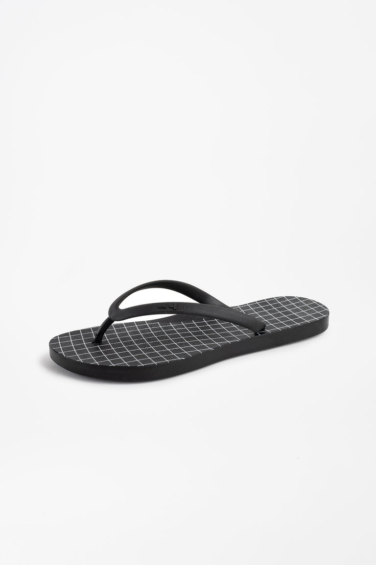 Side view of women's black flip flops with white grid pattern