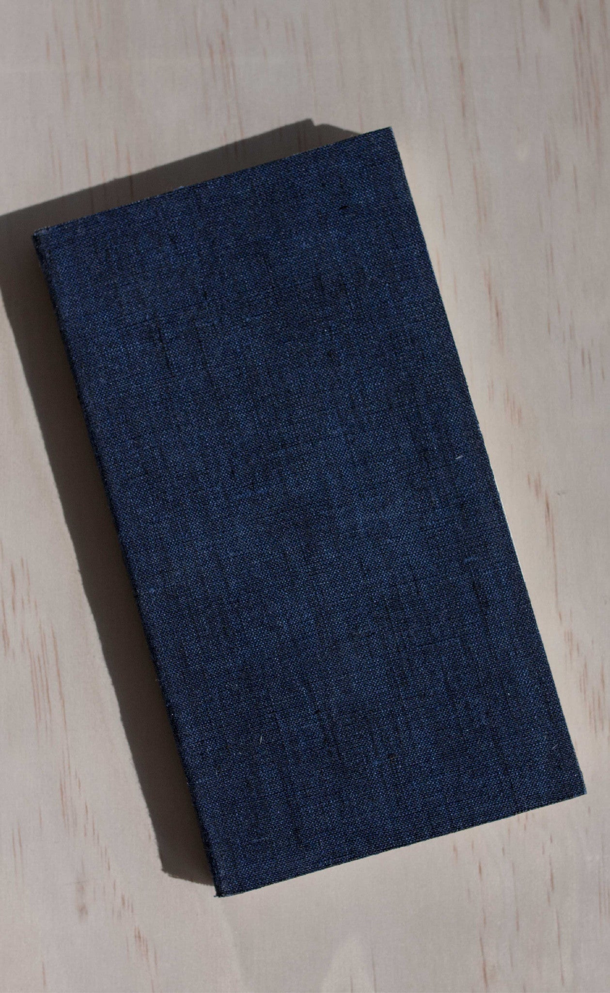 Flat lay view of the tall sized pocket notebook in dark navy linen.