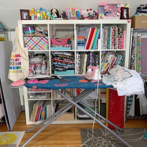 Marshmueller studio pressing area with ironing board and fabric shelving