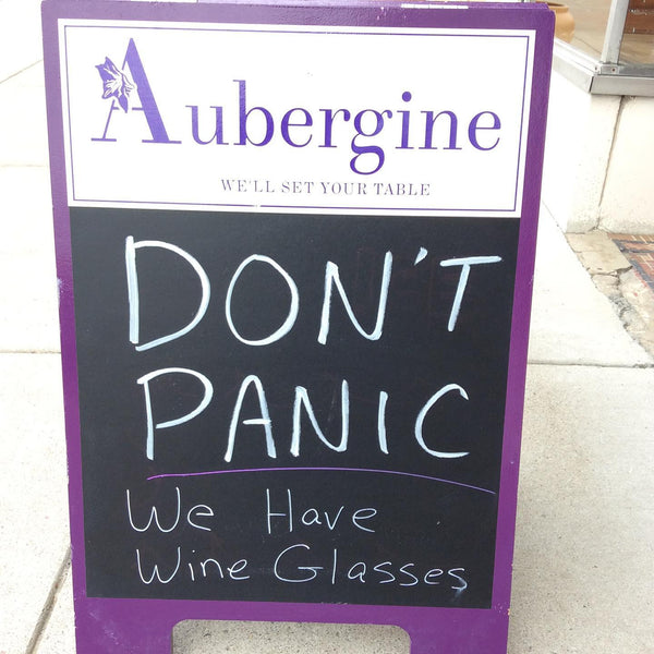 "Aubergine sandwich board with the words written in chalk, ""DON'T PANIC We have wine glasses"""