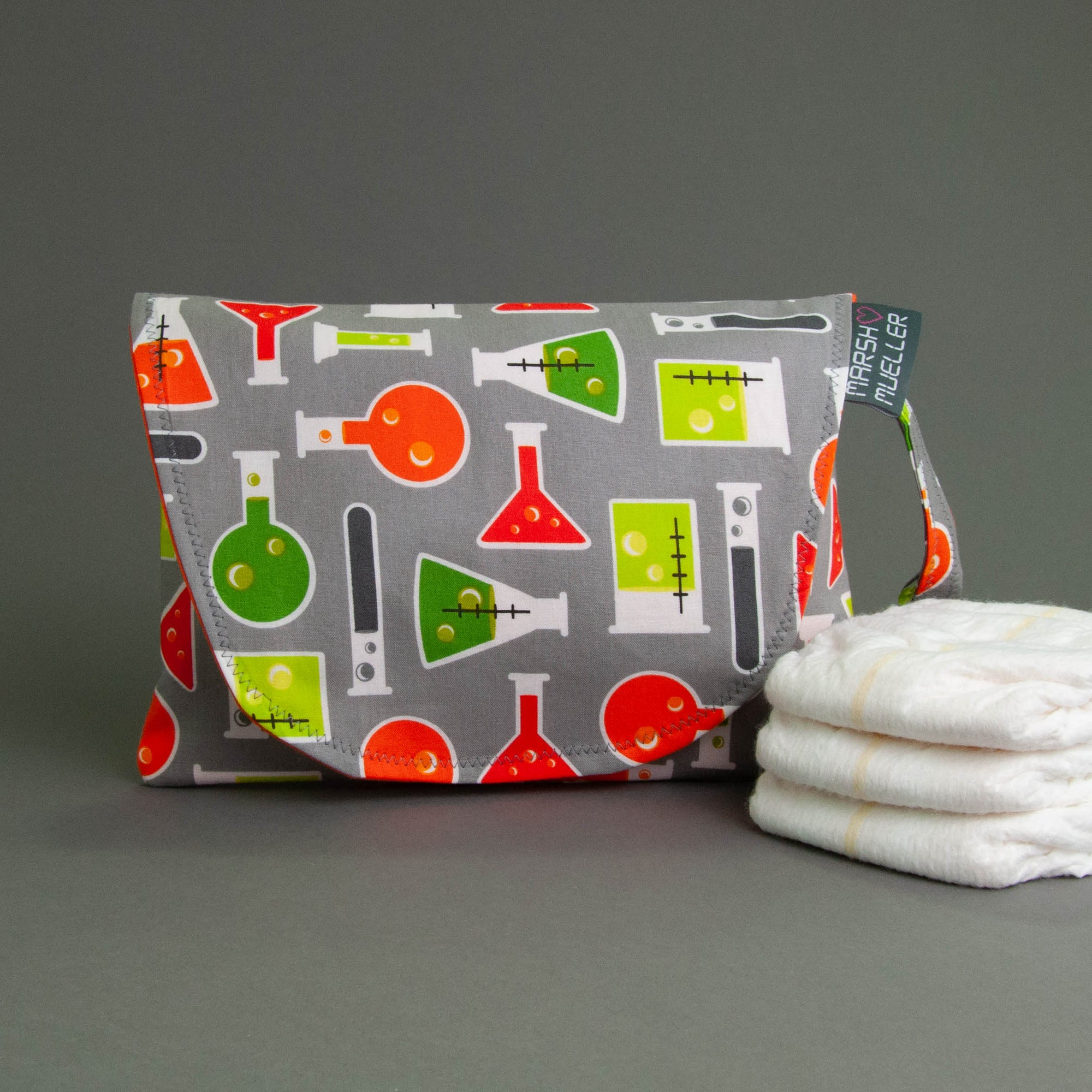 image of Marshmueller Diaper + Wipe Clutch in a bright beakers and flasks print fabric on a grey background with three diapers stacked to the right side
