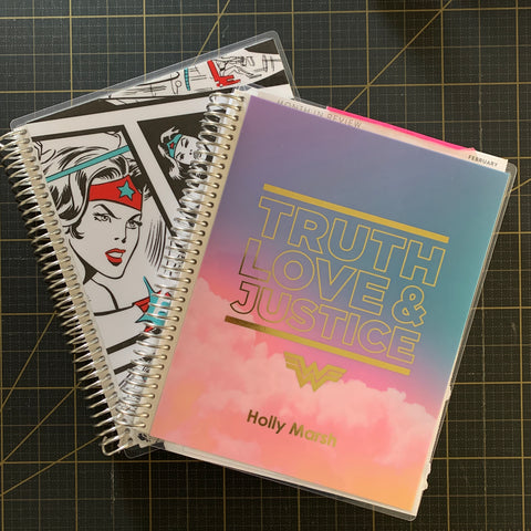 image of two Erin Condren coiled notebooks with Wonder Woman designs on their covers on a dark grid background