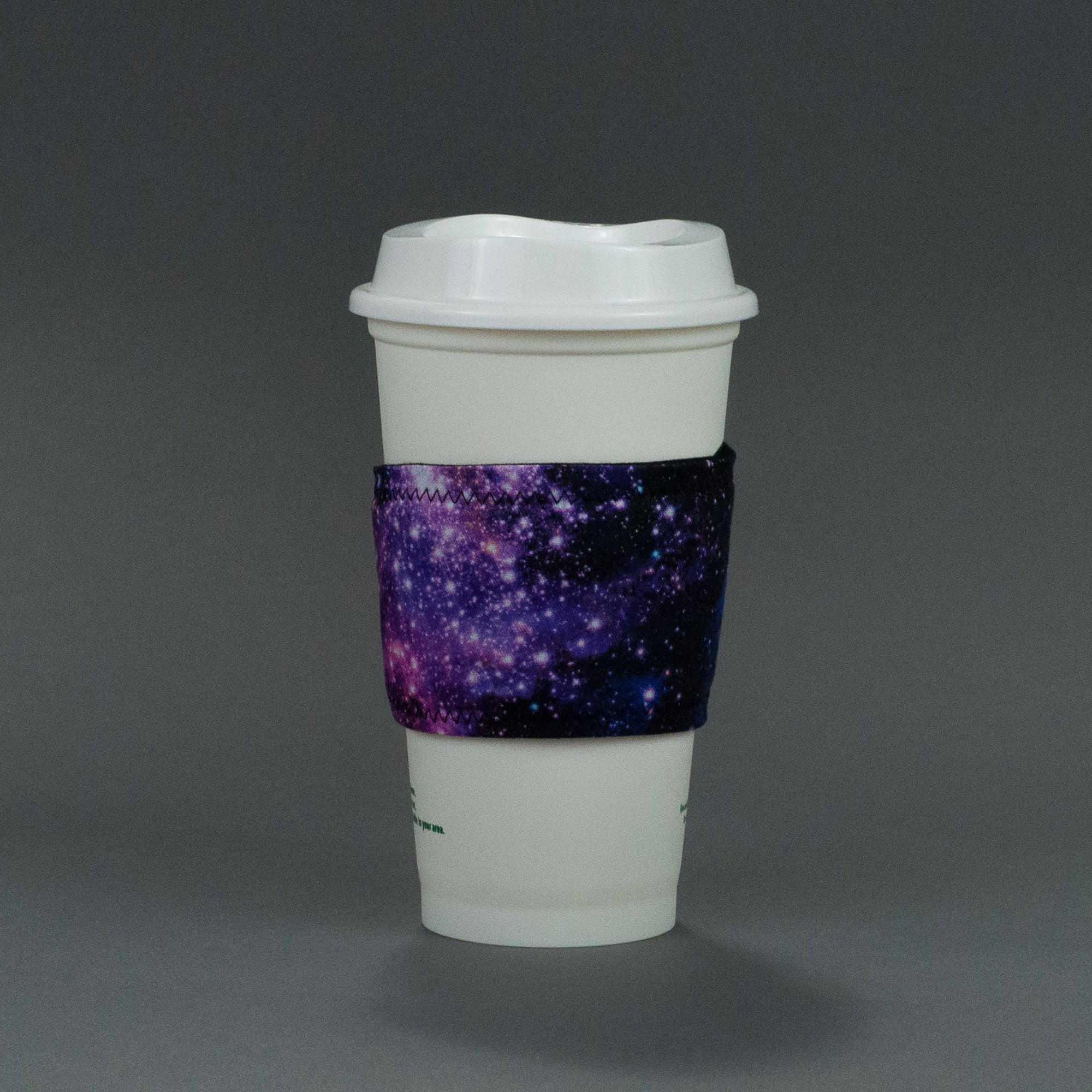 Image of handmade coffee cup sleeve on a white travel coffee cup on a grey background