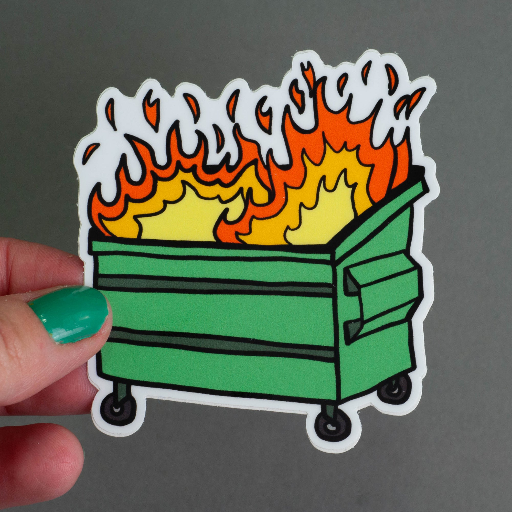 Image of hand holding a die cut sticker of a dumpster fire on a grey background