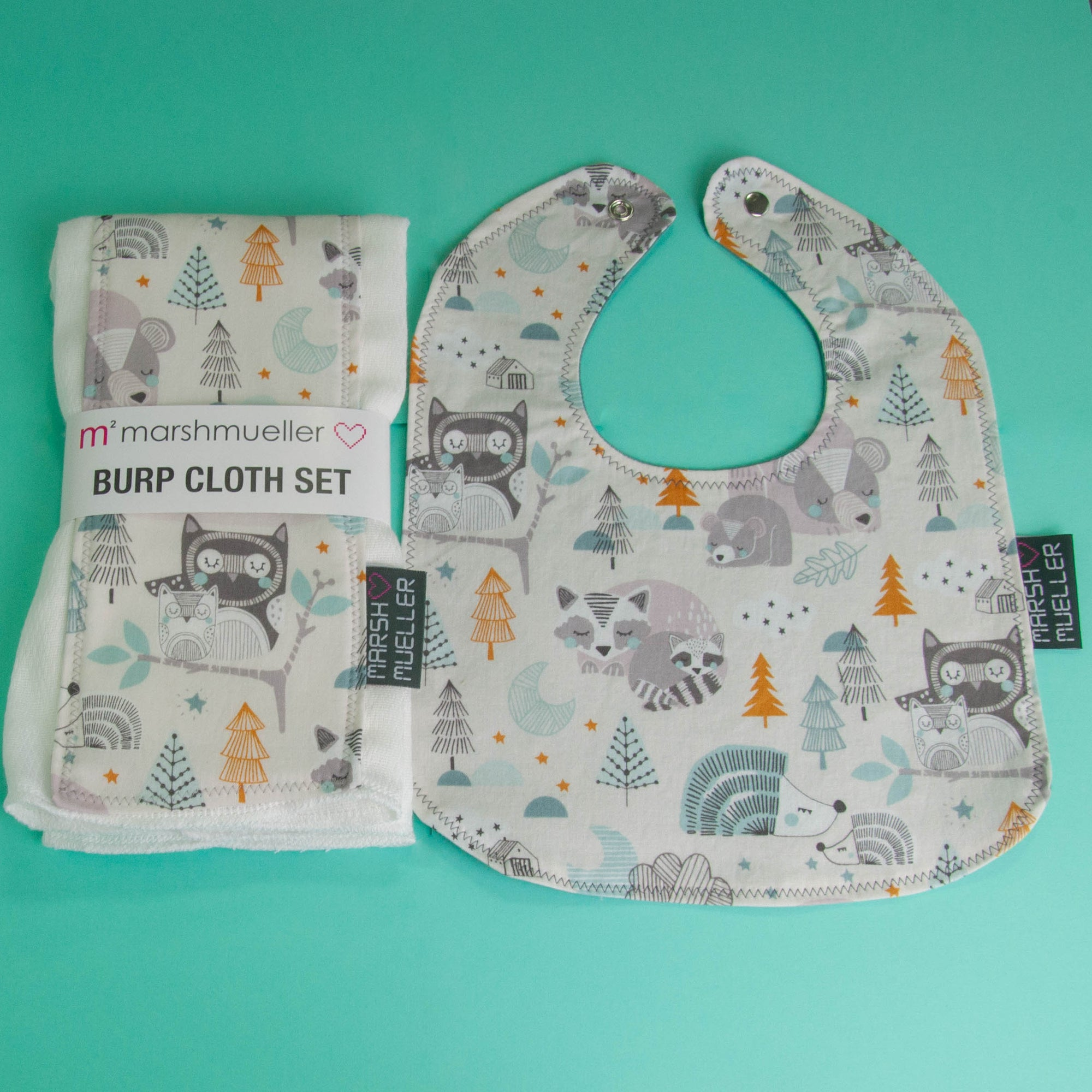 Image of Marshmueller Bib and Burp Cloth Set flatlay on a seafoam green background. The Bib and Burp Cloth Set are made from a woodland animals print fabric that is grey, teal, and mustard.