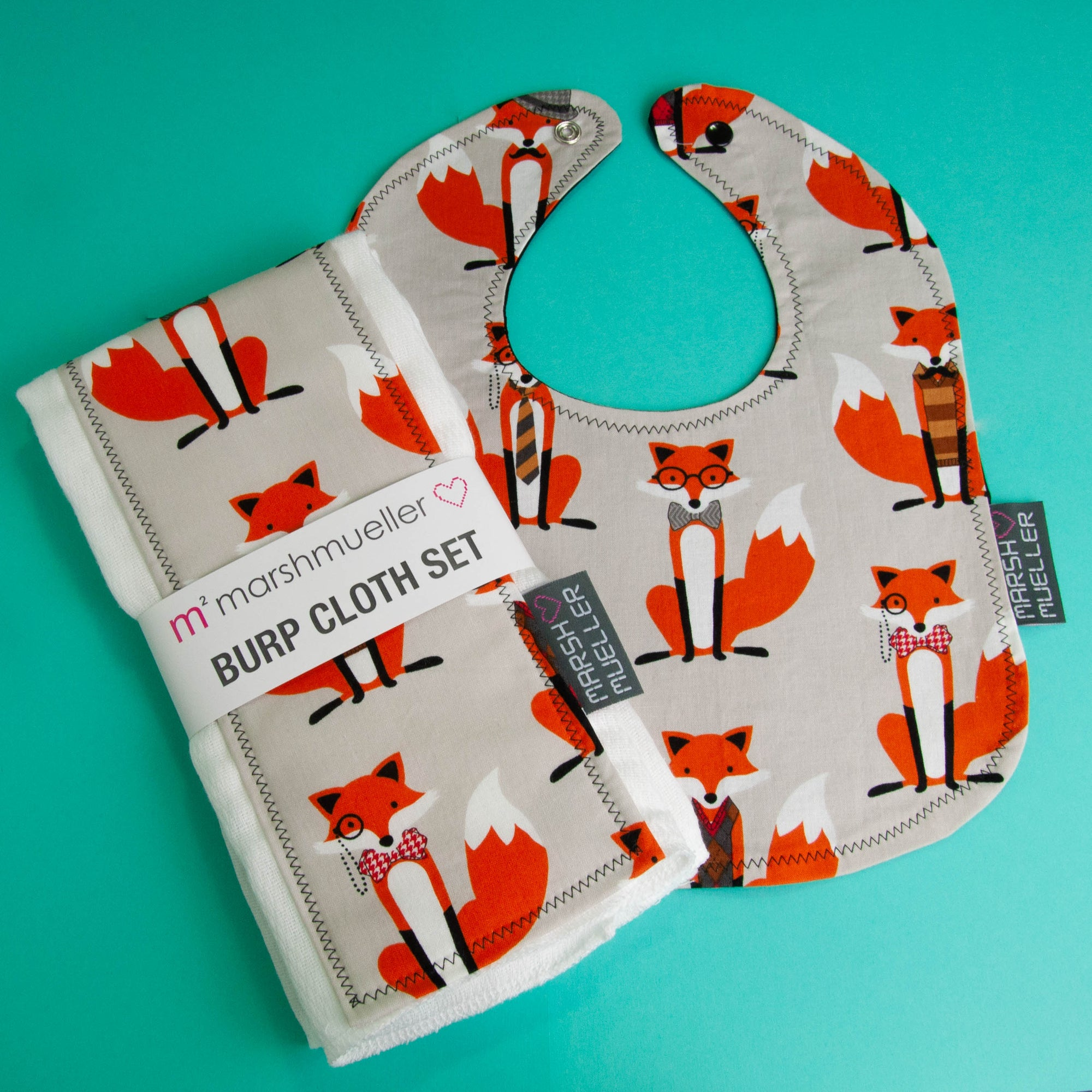 image of Marshmueller burp cloth set and bib flatlay made from an orange fox fabric with a grey background. Products are on a bright teal solid background