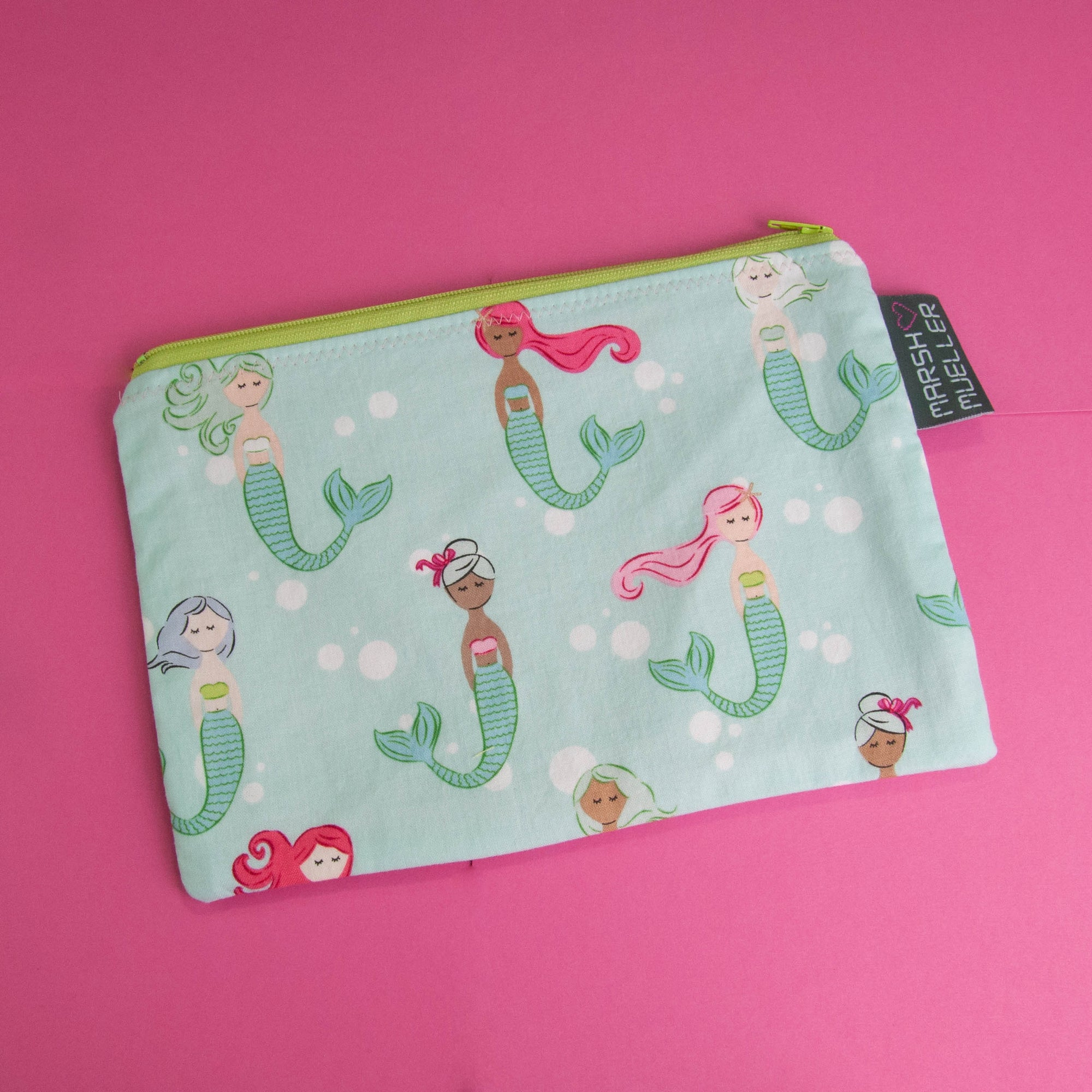 Image of Marshmueller Zipper Pouch made from a mermaids fabric. Image is on a pink background.