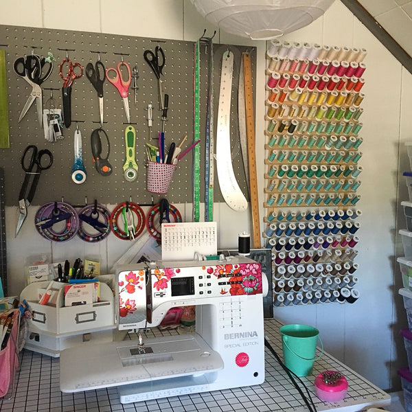 Marshmueller Studio sewing area with sewing machine, pegboard tool storage, and thread rack