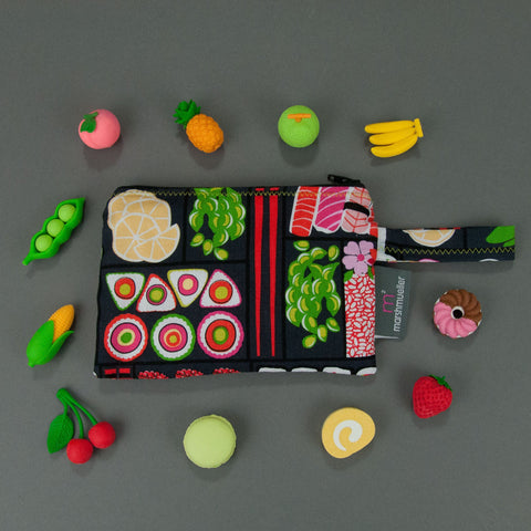 Bento Box Reusable Snack bag with little fruit erasers around it on a grey background