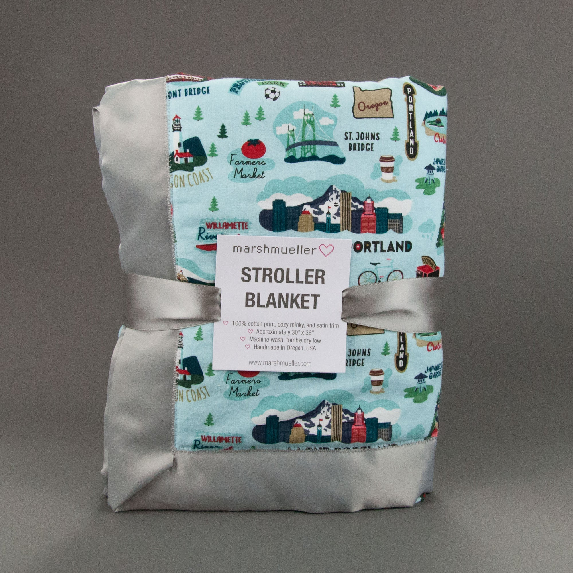 "Marshmueller Stroller blanket, folded into quarters, with blue Oregon print fabric and grey satin blanket binding. It is packaged with a grey satin ribbon and tag that says ""Stroller Blanket."" Blanket is standing up on short end on a grey background."