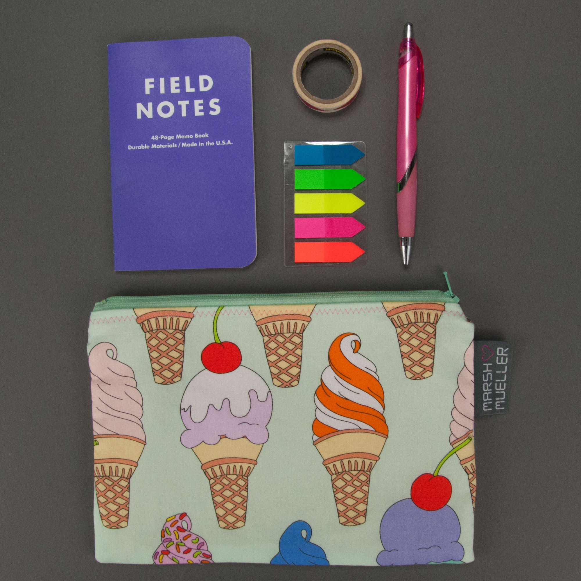 Image of flatlay of Marshmueller Zipper Pouch made from an ice cream print fabric with a notebook, washi tape, sticky flags, and a pink pen placed above the Zipper Pouch. Image is on a grey background.