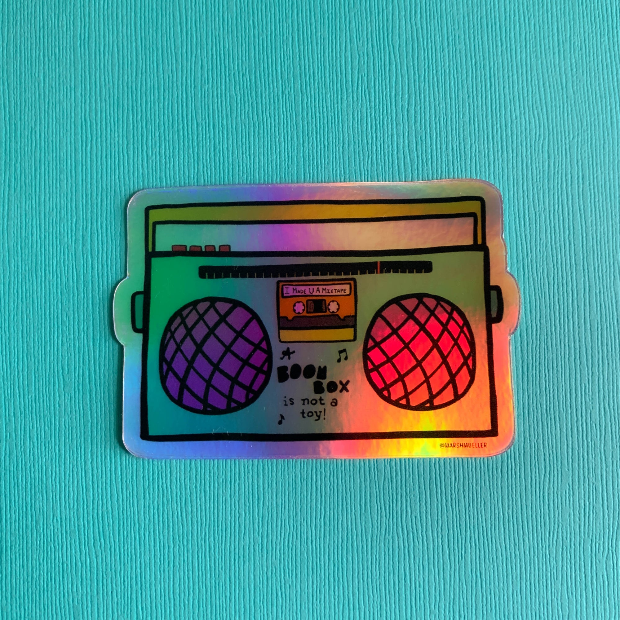hand holding a holographic die cut sticker of a boom box illustration on a pink background