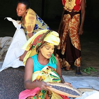 colorfully dressed women sorting cacao beans