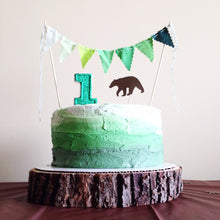 green glitter candle on bear cake for a bear first birthday party