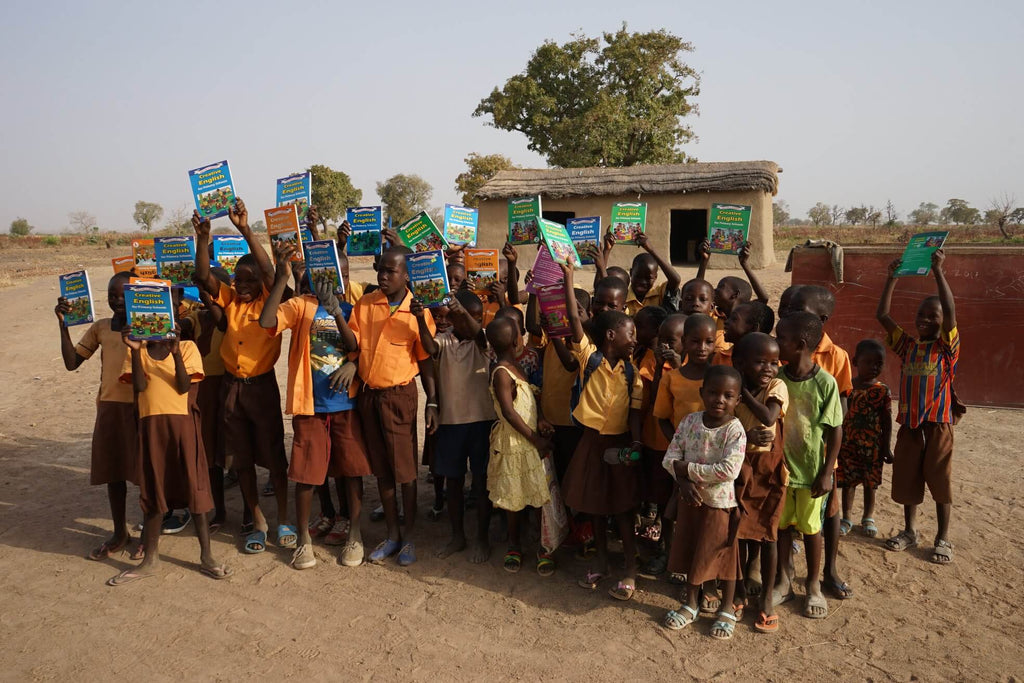 Children in front of school with textbooks, in Ghana, Bold Tuesday and Mondo charity